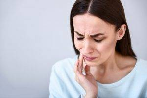 Serious problem. Cheerless sick woman touching her jaw and having a tooth ache while standing isolated on white background